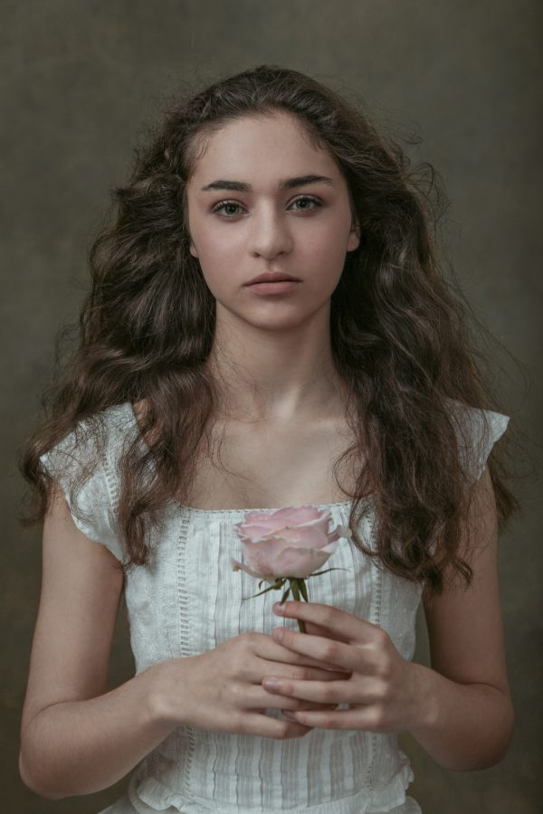 Beautiful girl with a rose in her hands